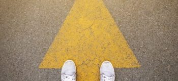 PLM Guide is shown by a man wearing white sneakers standing on a yellow arrow. The picture is taken from a birds eye view only showing his feet on the ground