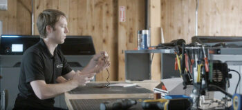 Working on a personalized prosthetic arm at a workbench