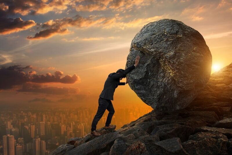 man pushing boulder uphill at sunrise