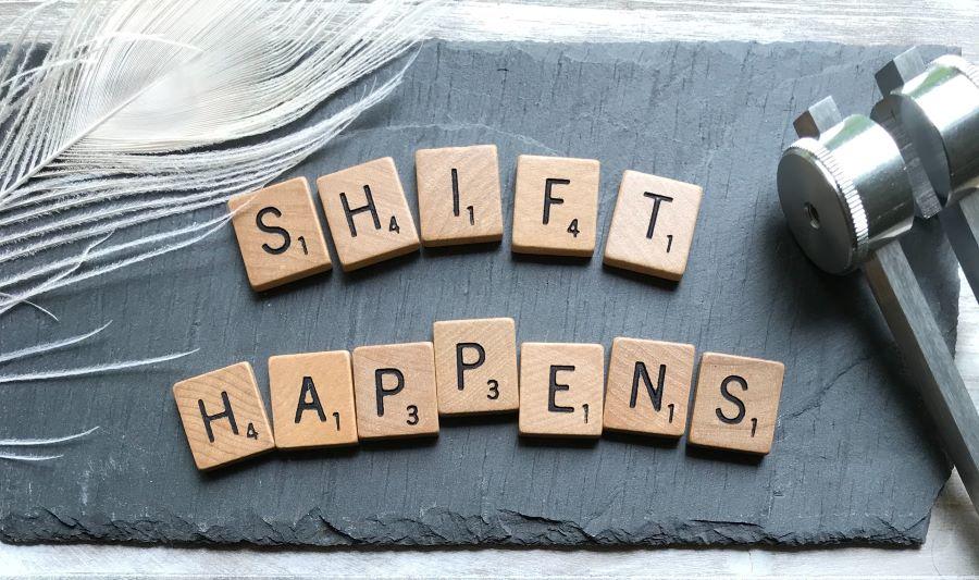 scrabble tiles spelling 'shift happens'