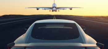 Black and gray luxury car chases airplane down stripped runway into the yellow and orange sunset. This relates to E/E Systems Development and Electrical Systems with Capital by encapsulating both the Aerospace and Automotive industry into one image as well as how we are continually moving forward with solutions for our customers. E/E Systems industry articles automotive aerospace