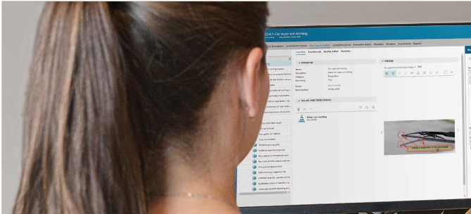 worker looking at computer screen showing Teamcenter Quality Management software