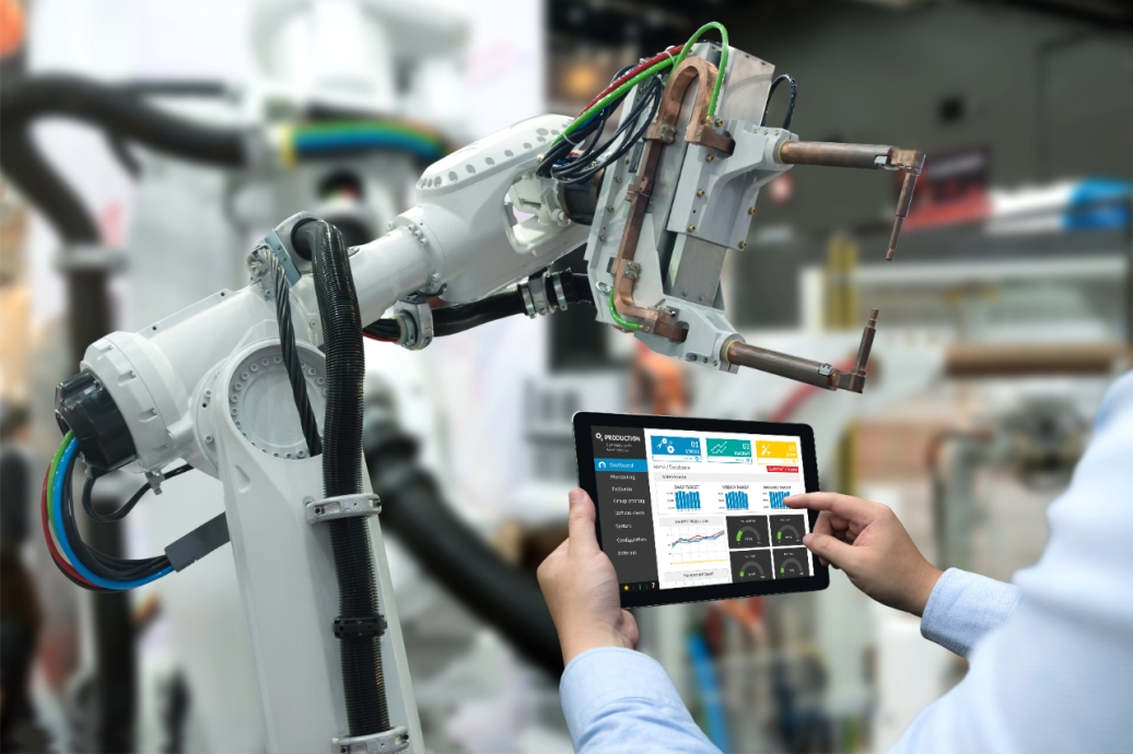 engineer using tablet with manufacturing operations management software to interface with robot arm in a smart factory