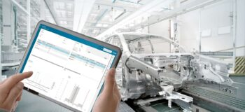 automobile assembly worker reviewing supplier quality management data on a tablet