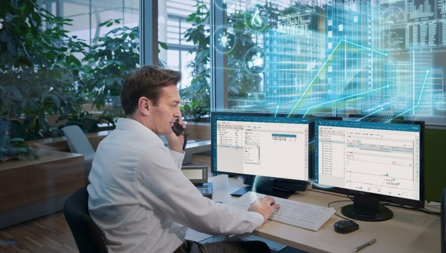 quality manager sitting at his computer reviewing using quality and spc software
