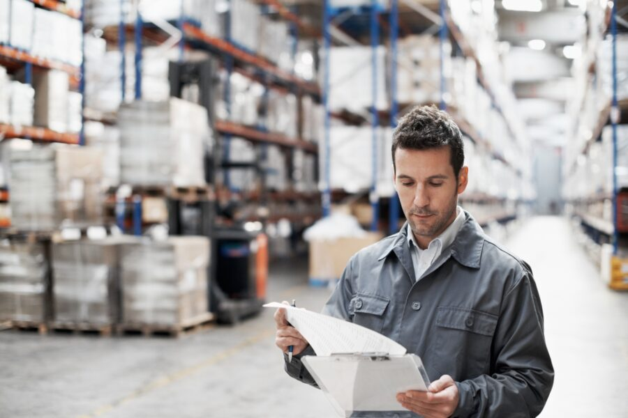Man checking inventory in a warehouse. He has employed a make-to-stock strategy instead of make-to-order.