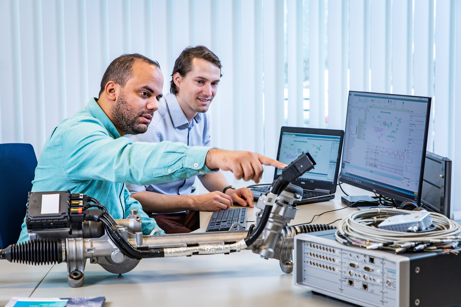 two engineers work at a desk performing the blend of test and simulation that is called model-based system testing