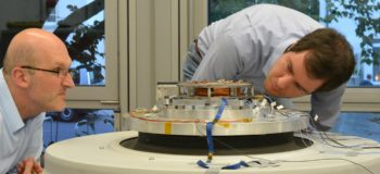 RWTH professors and future engineers examine a satellite piece fitted on a shaker table