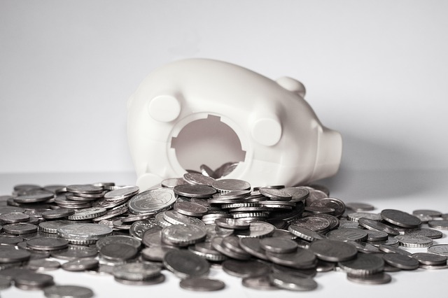a fallen-over piggy with coins all over the ground as an example for wasting money