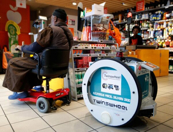 A man does his own shopping at a store using an autonomous robot, shaped and inspired by Star Wars R2D2, in a test for the delivery of groceries by Franprix supermarket chain in the 13th district of Paris, France, April 17, 2019.  REUTERS/Charles Platiau