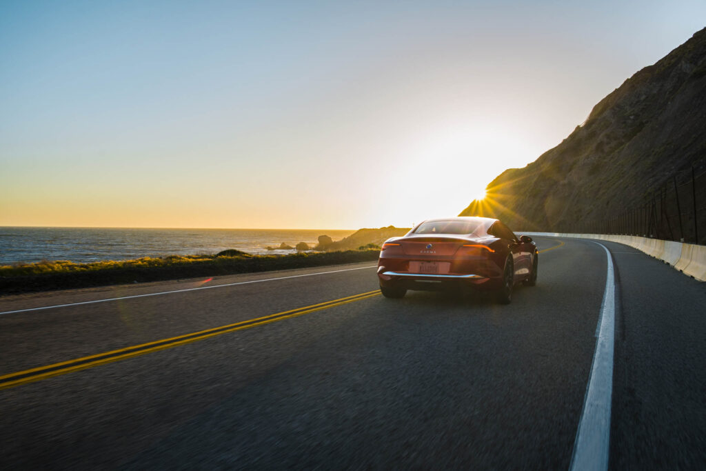 A Karma Revero GT drives towards to the setting sun