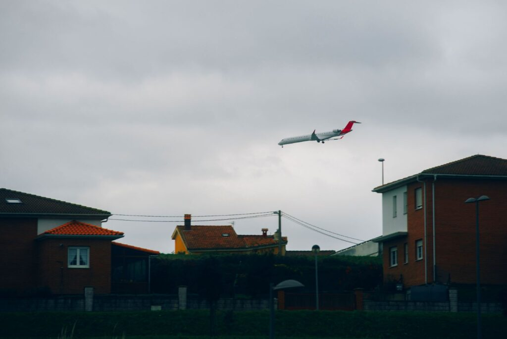 An airplane flies over a residential area.