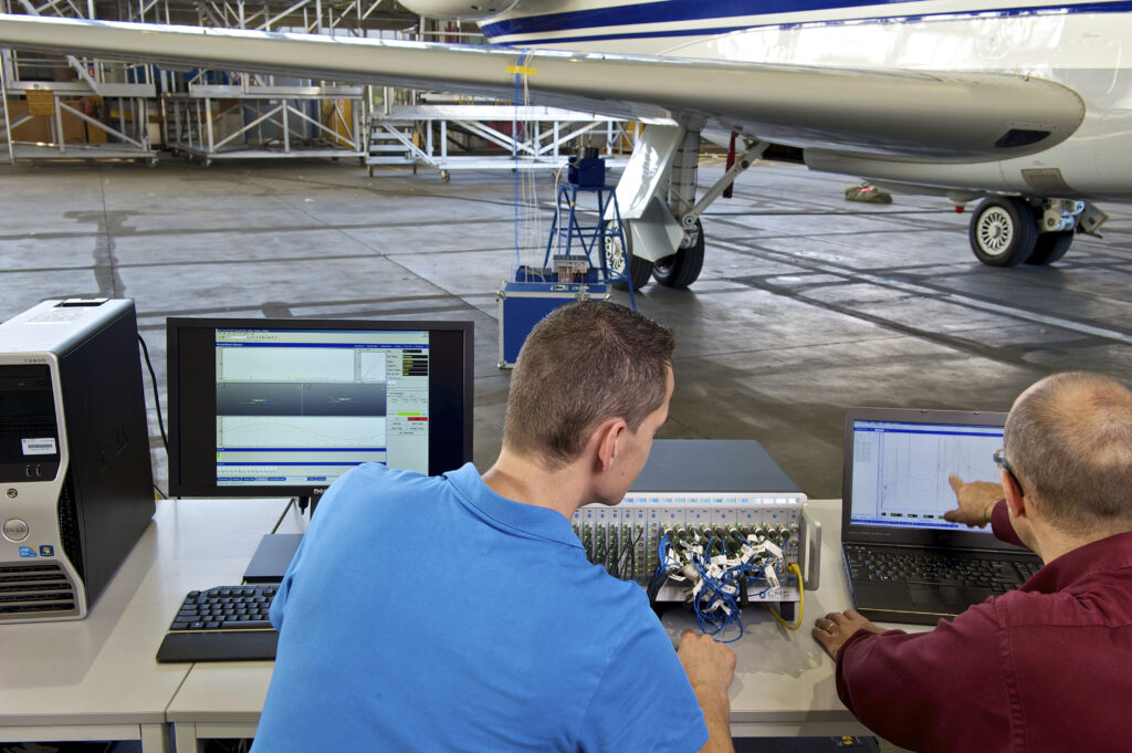 Engineers perform a ground vibration test on an aircraft using modal testing equipment