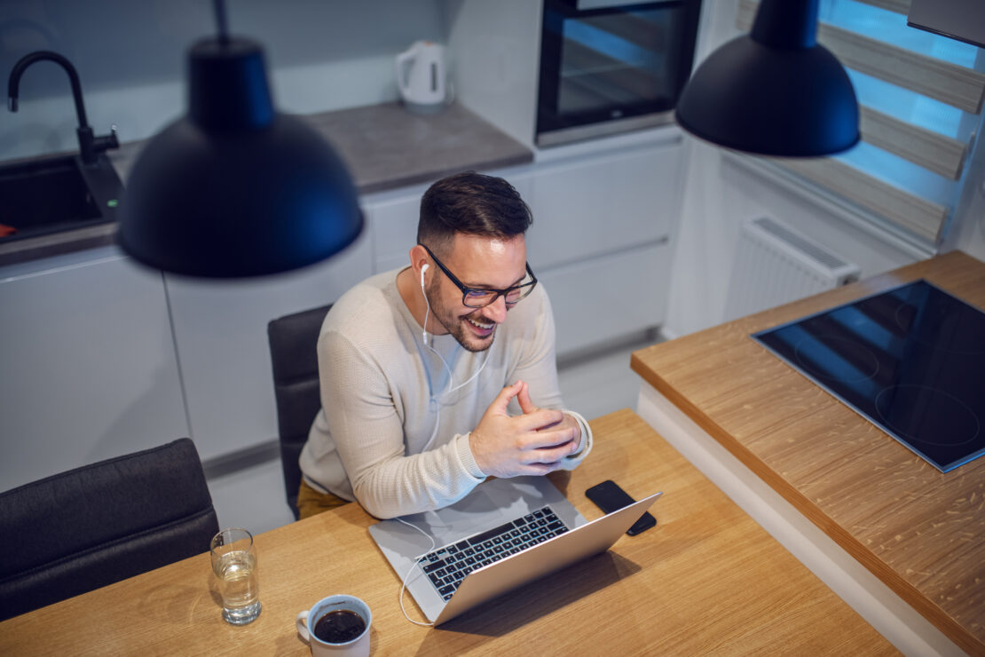 Top view of attractive smiling caucasian man sitting at dining table in kitchen and having video call with his girlfriend. On table are laptop, glass with water and mug with coffee.