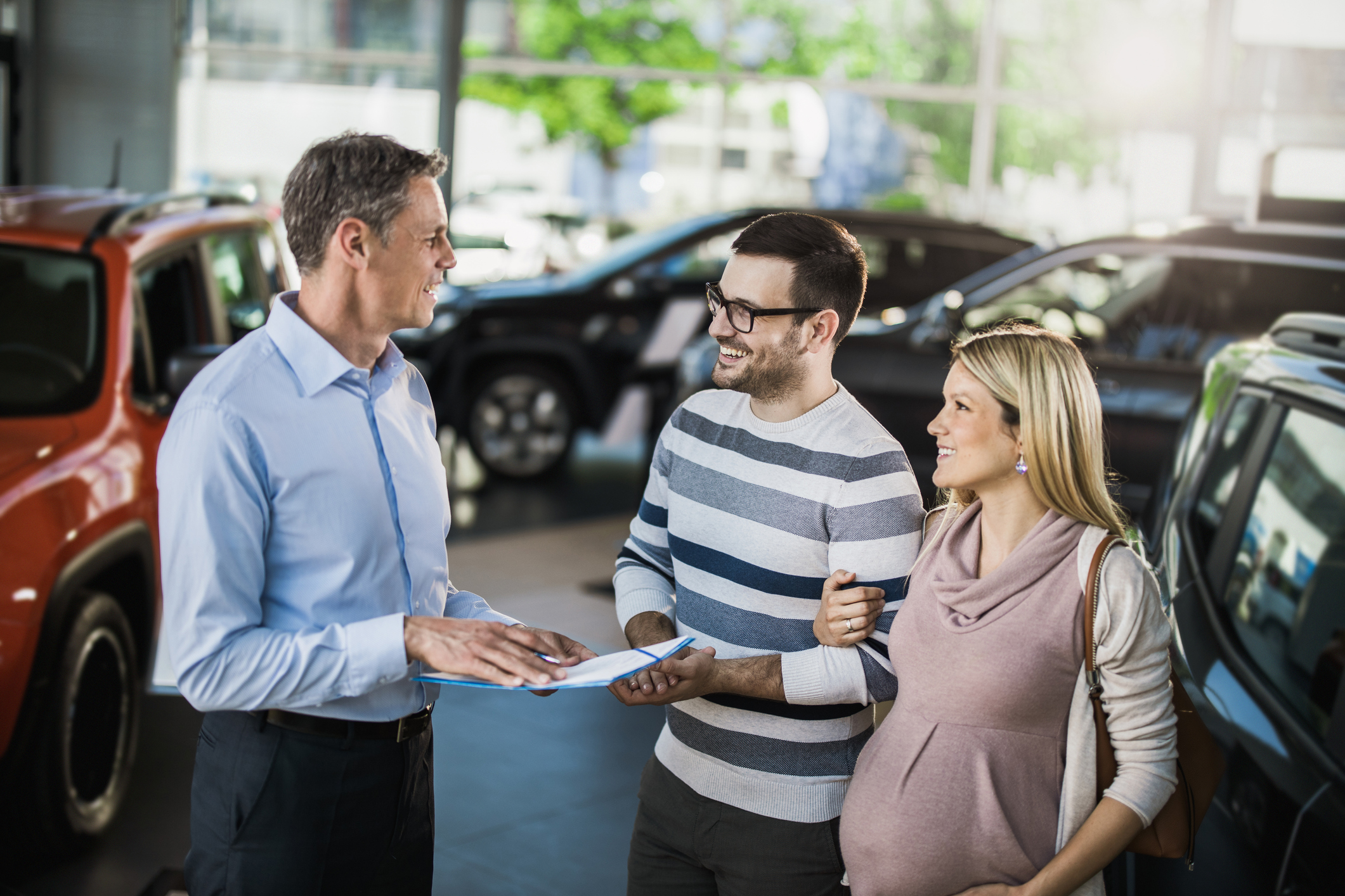 A happy couple talks to a car vendor in a car dealership.