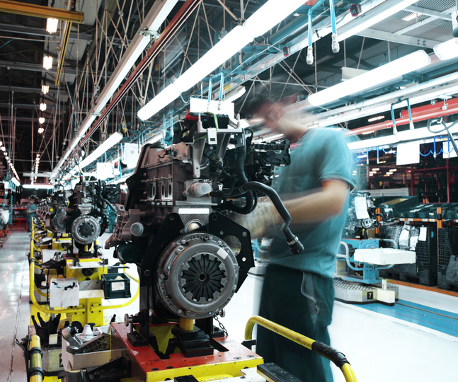 A man works on an engine in the production line