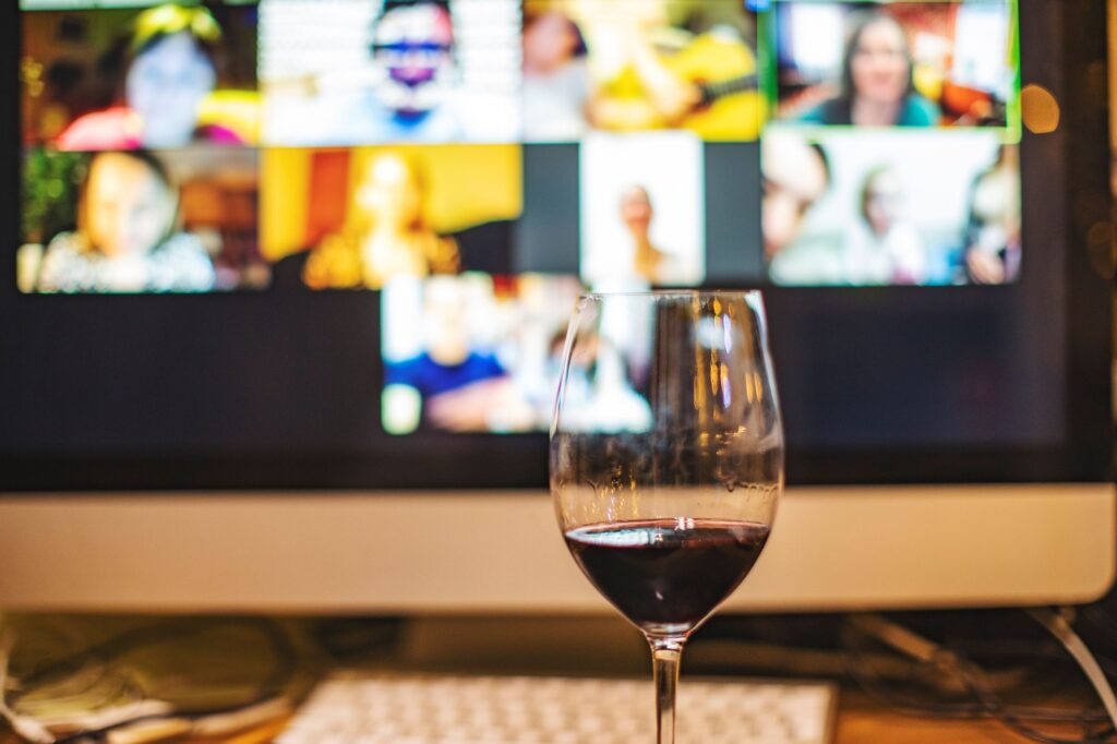 A glass of wine is set in front of a computer displaying a virtual meeting room.