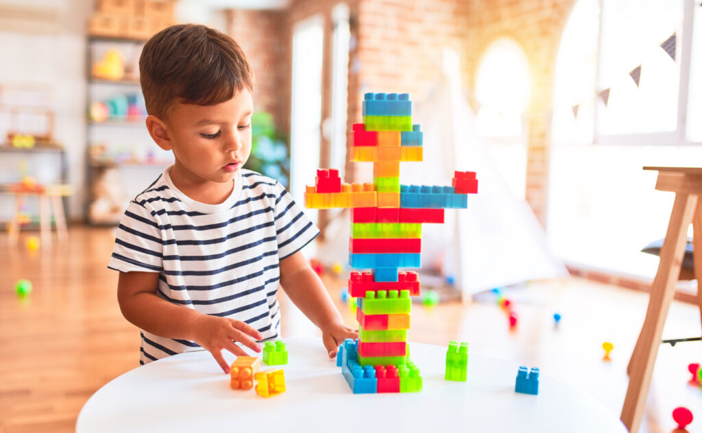 A young boy assembles Lego blocks