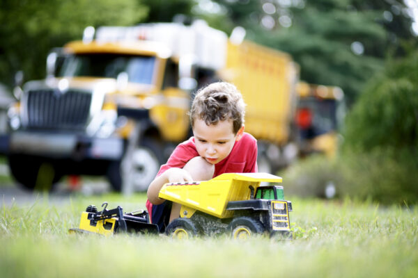 Young boy plays with a toy truck in the garden. The toy seems to withstand all harsh conditions.