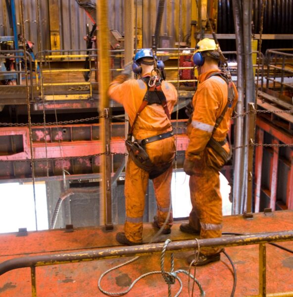 Two oil and gas industry workers wearing safety equipment